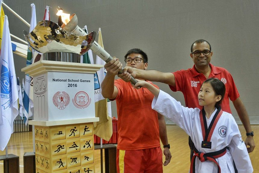 Minister of State for Education and Communications and Information Janil Puthucheary lighting the cauldron with torch bearers Almanda Mik and Eric Yee at the Opening Ceremony of the 2016 National School Games yesterday.