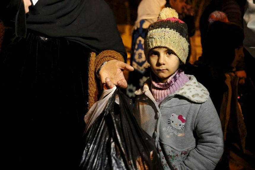 A Syrian girl waits with her family, who say they have received permission to leave the besieged town of Madaya.