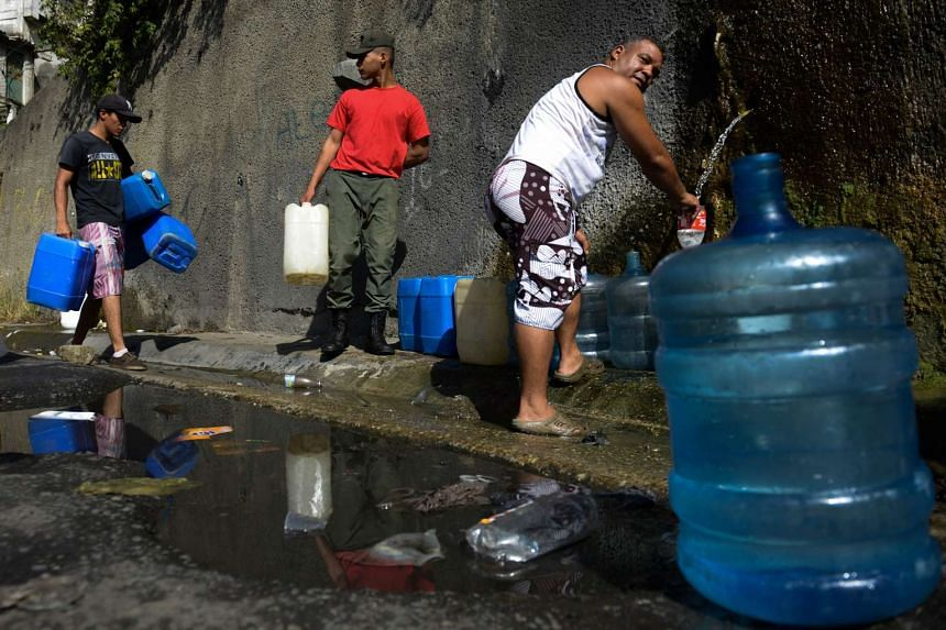 People lining up to fill jerry cans with water from the Wuaraira Repano mountain in Caracas, Venezuela.