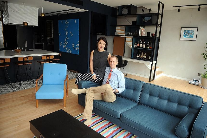 A blue kitchen with Peranakan floor tiles (left) segues into the living room of the apartment of Mr Darren Sabom and Ms Sharon Siah (both above). The master bedroom sports a monochrome palette and has little furniture besides the bed and walk-in ward