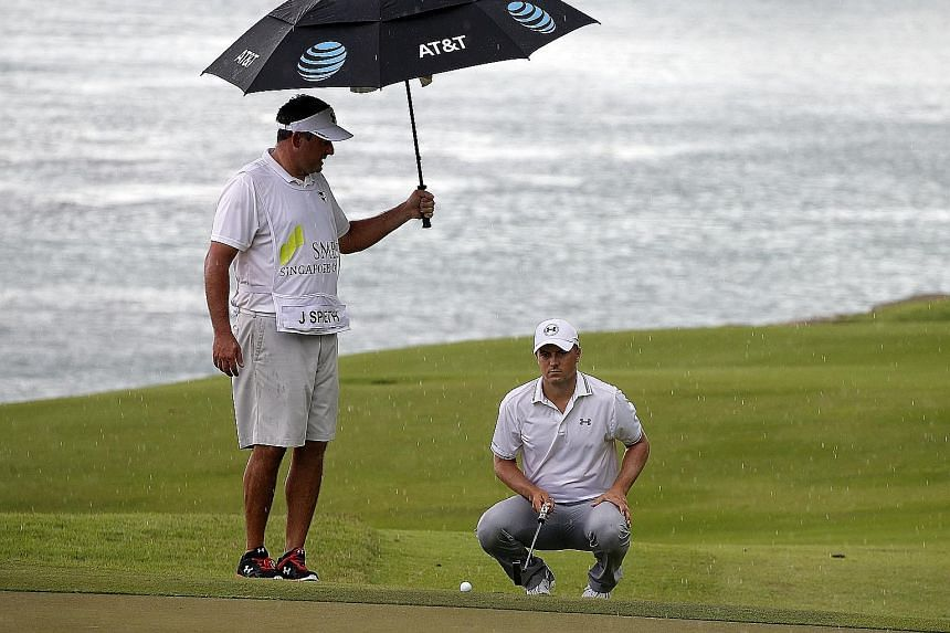 Jordan Spieth taking shelter from the rain under the umbrella of manager and stand-in caddie Jay Danzi at the SMBC Singapore Open yesterday. After a fine opening 67, he was even par after six holes when play was called off. He and 77 others will resu