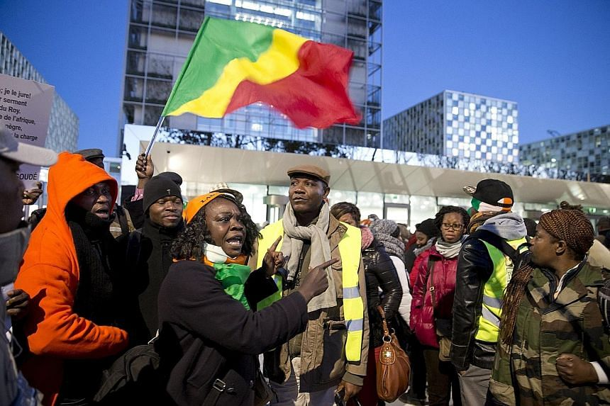 "Supporters of Laurent Gbagbo and Charles Ble Goude rallying outside the International Criminal Court on Thursday. The ICC prosecutor vowed on Wednesday to ""leave no stone unturned"" in investigating alleged crimes committed by all sides in Ivory Coast"