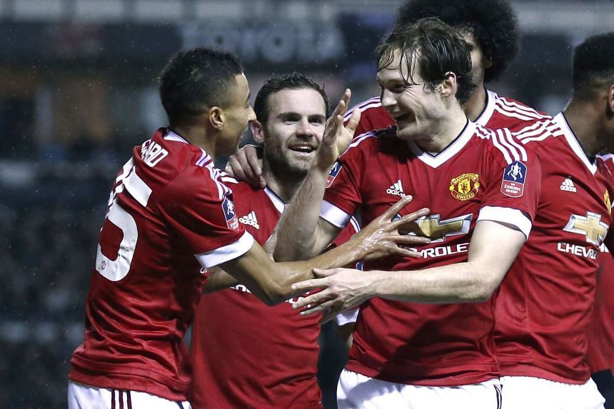 Daley Blind celebrates with team mates after scoring the second goal for Manchester United.