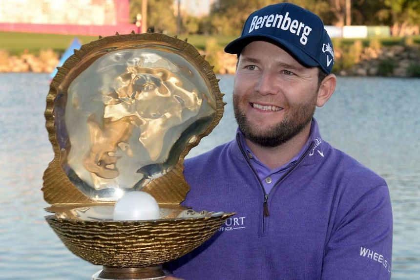 Branden Grace of South Africa poses with the winners trophy after the final round of the Qatar Masters.