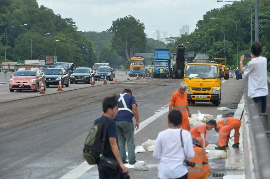 A cleanup crew (right) soaking up oil using absorbent sheets, while workers replace the tarmac on the BKE (background).