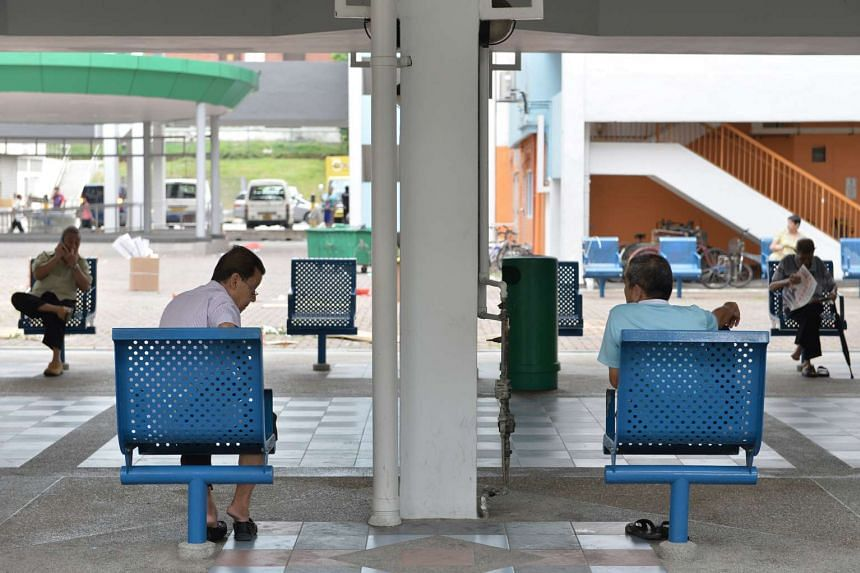 Elderly men sitting on benches at the foot of a block in Chin Swee estate.