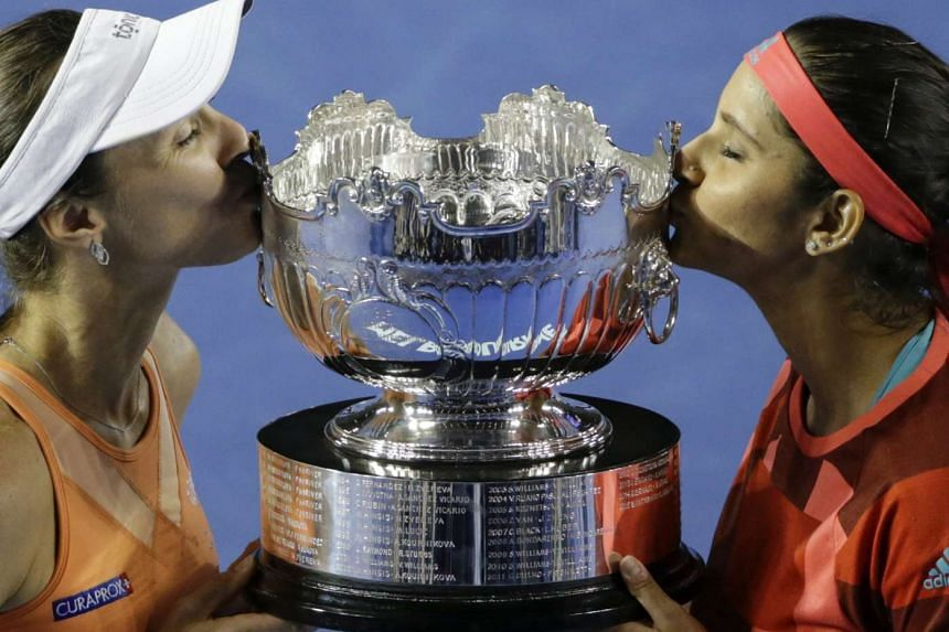 Martina Hingis (left) and Sania Mirza kissing the Australian Open women's doubles trophy after defeating Andrea Hlavackova and Lucie Hradecka 7-6, 6-3 in the final yesterday. Their winning run is now 36 matches, the third-best in WTA history.