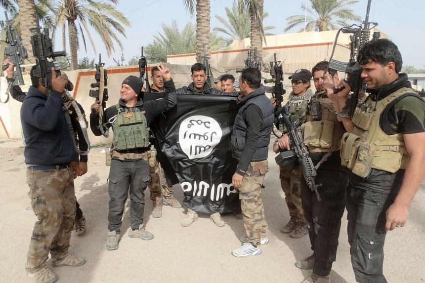 Iraqi security forces with an Islamic State in Iraq and Syria flag which they pulled down in the city of Ramadi, on Jan 19. Such victories have made Pentagon officials more optimistic about the effectiveness of Iraqi forces if they are trained by Ame