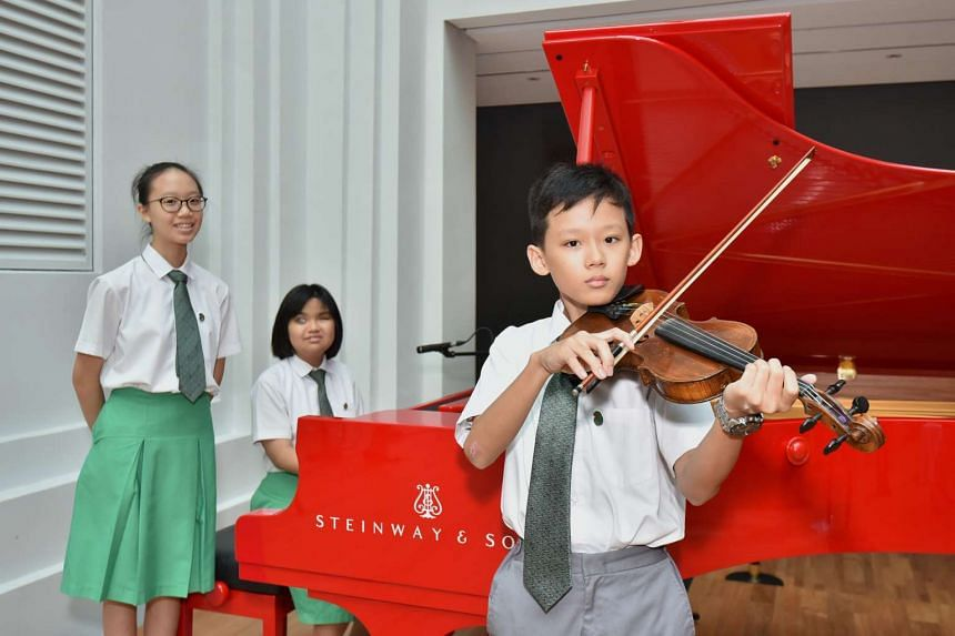 Performers from Ahmad Ibrahim Secondary School (from left) Jessie Phay, 13, Adelyn Koh, 15, and Koh Ming Yang, 13, at the National Gallery Singapore yesterday.