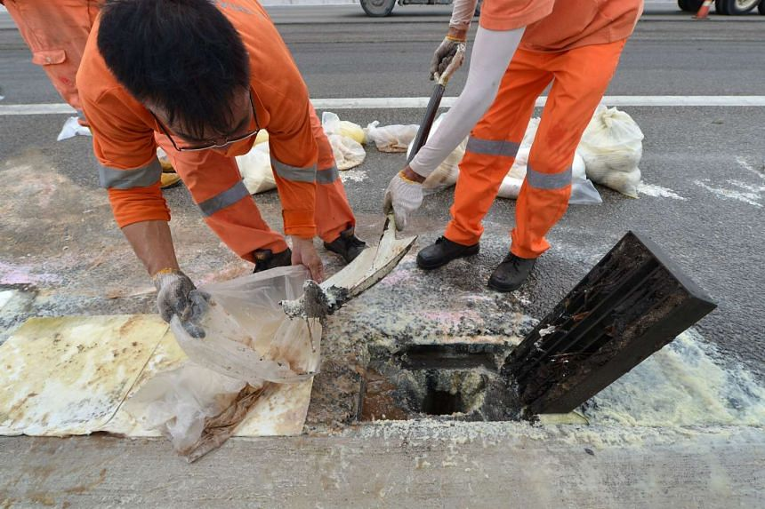 The cleanup crew (above) removing the spilled oil by the side of the Bukit Timah Expressway, and a drain under the expressway filled with yellow oil. A Malaysian-registered palm-oil tanker was involved in a collision with a car at about 3am yesterday