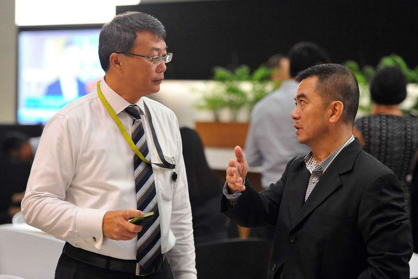 A Singapore Exchange staff member (with tie) and president of The Society of Remisiers (Singapore), Mr Jimmy Ho, at the Equities Dialogue on Thursday. Senior SGX figures held a closed-door meeting with about 100 remisiers on the same day.