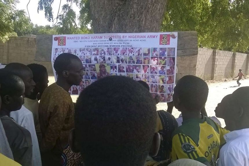 People looking at pictures of wanted Boko Haram suspects on a notice posted by the Nigerian military, in Maiduguri on Nov 13, 2015.