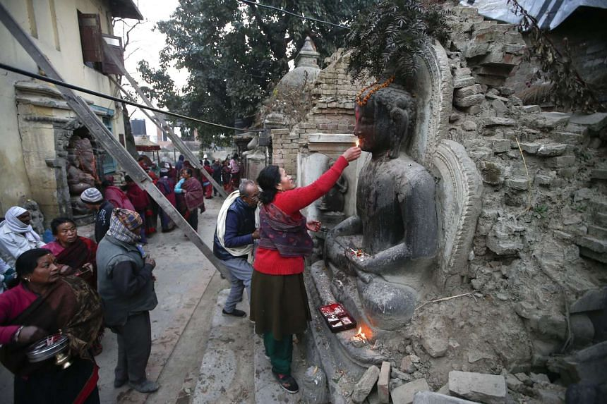 A Nepalese woman worshipping a partially destroyed statue of Lord Buddha in Bhaktapur, on the outskirts of Kathmandu, on Jan 24, 2016.