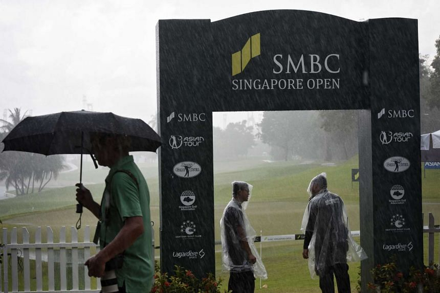 A photographer walks pass 2 security guards at the Serapong Course at Sentosa Golf Club after play was stopped due to bad weather during the final round of the SMBC Singapore Open held on Jan 31, 2016.