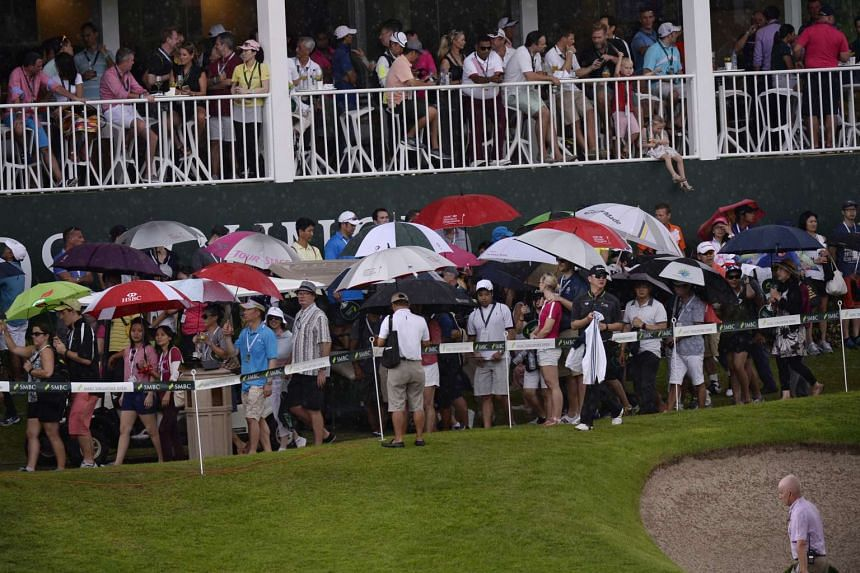 Spectators walk under umbrellas at Hole 18 at the Sentosa Golf Club's Serapong Course after play was stopped due to bad weather during the final round of the SMBC Singapore Open held on Jan 31, 2016.