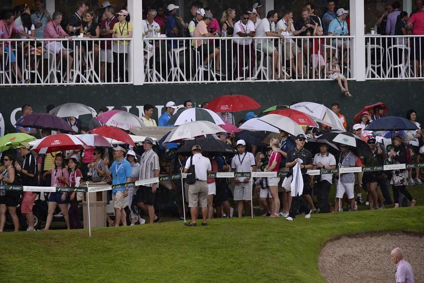 Spectators walk under umbrellas at the Sentosa Golf Club's Serapong Course after play was stopped due to bad weather during the final round of the SMBC Singapore Open on Jan 31, 2016.