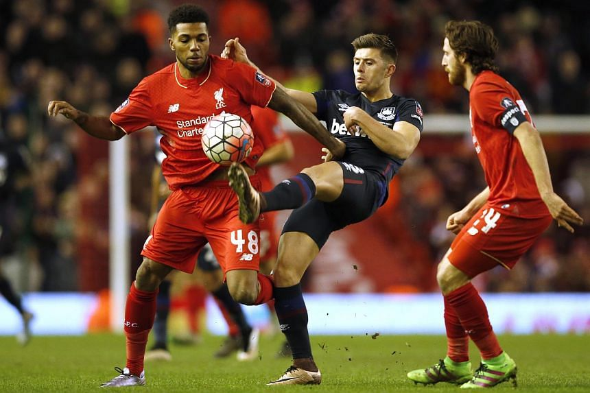 Liverpool's Jerome Sinclair (left) and West Ham's Aaron Cresswell (centre) vie for the ball during their FA Cup Fourth Round football match.