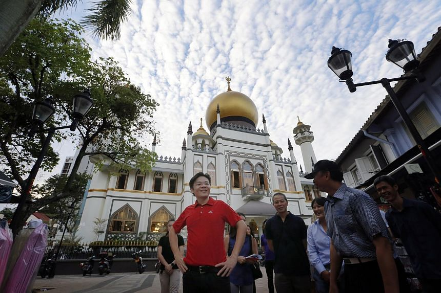 Minister for National Development Lawrence Wong (centre) visiting car-free zones at Kampong Glam and Liang Seah Street.
