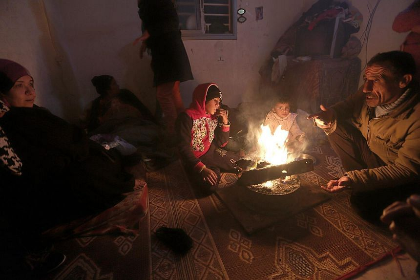 A family warms up in front of a fire as they endure the cold weather inside their temporary housing.