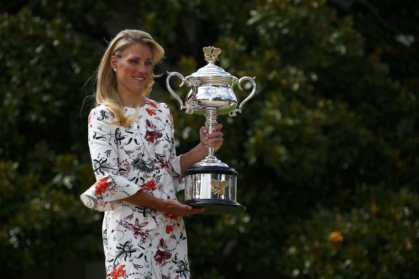 Kerber posing with her trophy at the Government House in Melbourne.