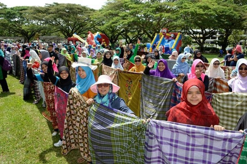 Participants holding up the knotted chain of sarongs, which measured 530m to set a record.