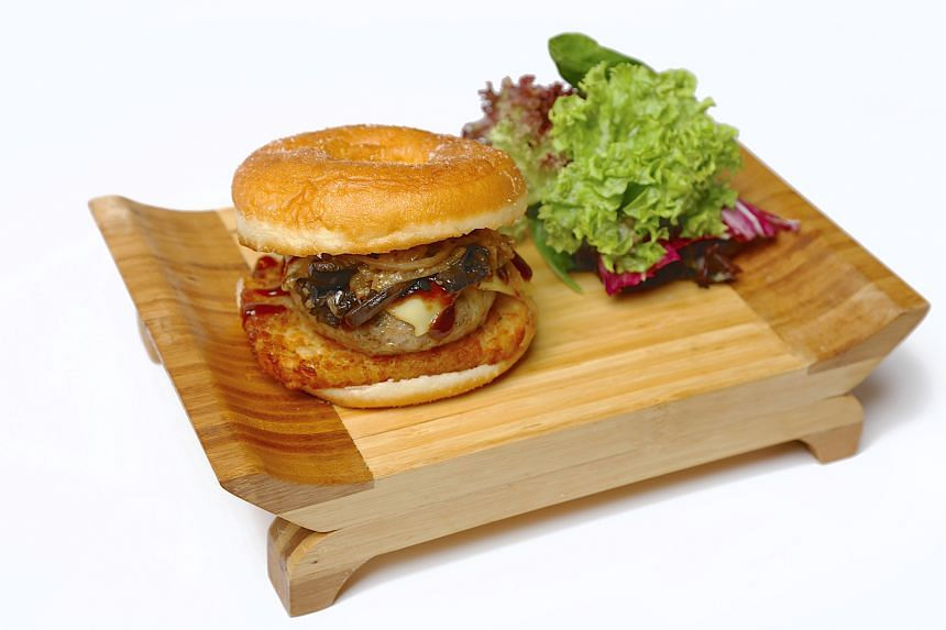 Donut Burger ($13) with chicken or beef topped with mushrooms, caramelised onions, hashbrown and barbecue sauce .