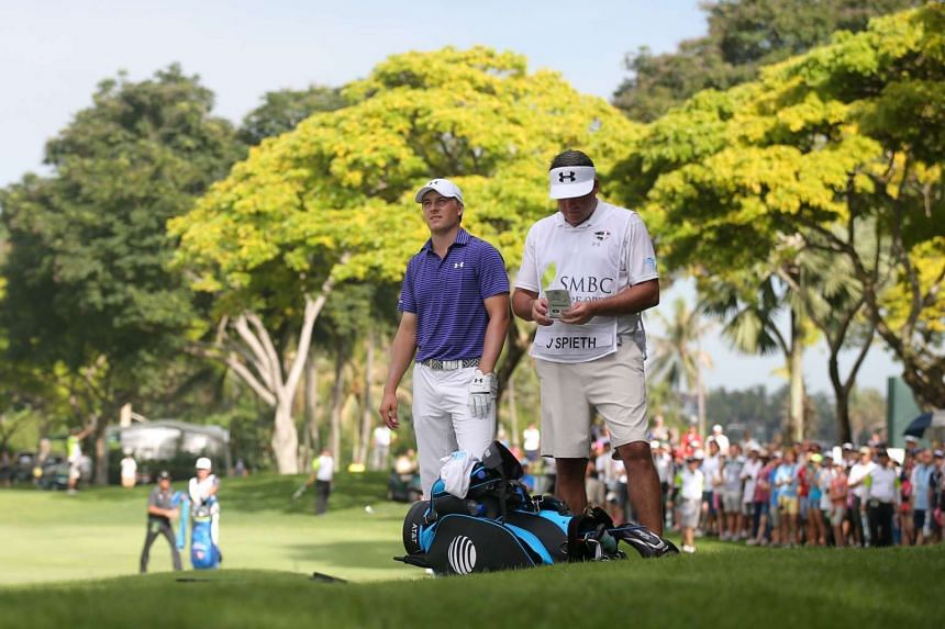 American Jordan Spieth assessing the situation while his caddy kept score during the third round of the SMBC Singapore Open yesterday. Going into today's final round, Spieth is three shots behind leader Song Young Han.