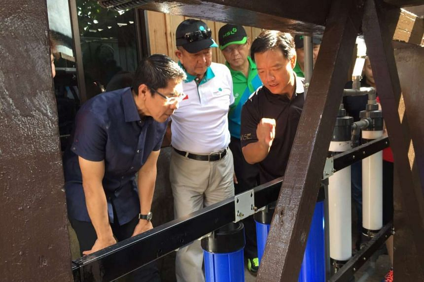 Demonstration and explanation of the water treatment system to grassroots advisor Dr Maliki Osman (left).
