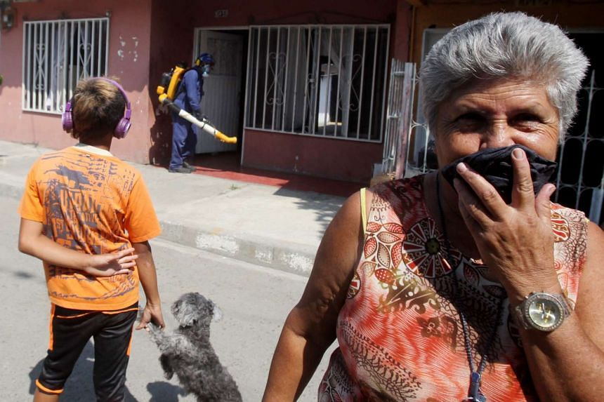 Residents wait outside as workers fumigate homes in Cali, Colombia, on Jan 28, 2016.