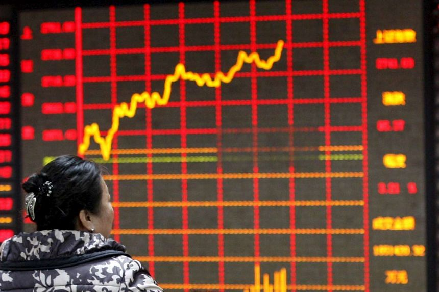 An investor looks at an electronic board showing stock information at a brokerage house in Huaibei.