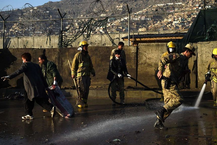 Afghan firefighter wash the site after a suicide attacker detonated himself at the entrance to a police base in Kabul on Feb 1, 2016.