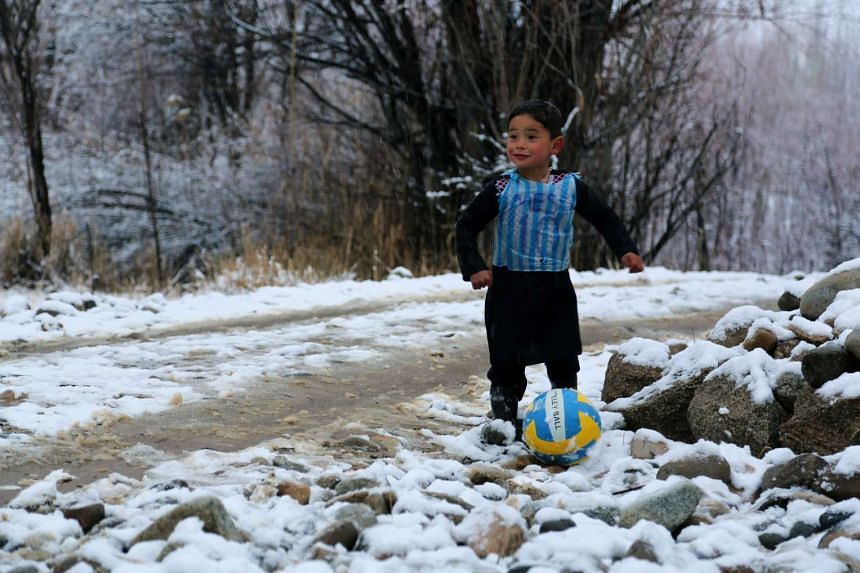 In this photograph taken on Jan 29, 2016, Afghan boy and Lionel Messi fan Murtaza Ahmadi, five, wears a plastic bag jersey as he plays football in Jaghori district of Ghazni province.