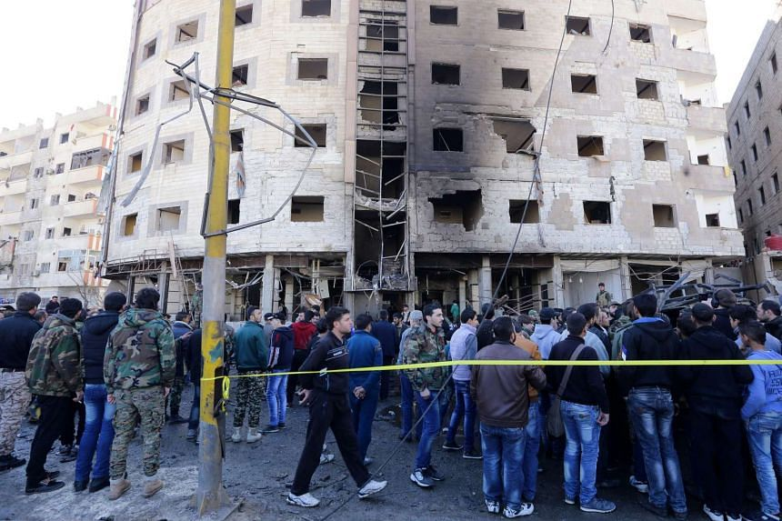 Syrian people and soldiers gather at the site of bombing in the district of al-Sayeda Zainab in Damascus, Syria, on Jan 31, 2016.