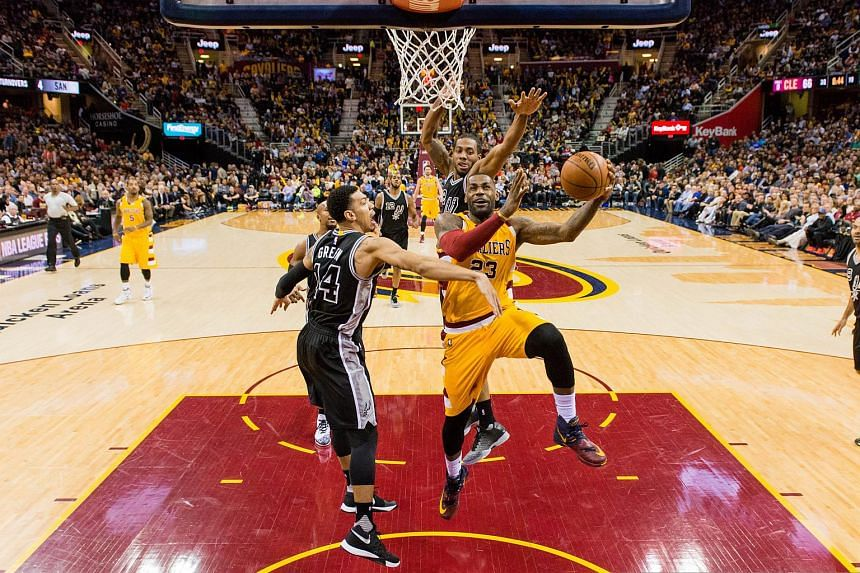 LeBron James #23 of the Cleveland Cavaliers shoots over Kawhi Leonard #2 and Danny Green #14 of the San Antonio Spurs on Jan 30, 2016.