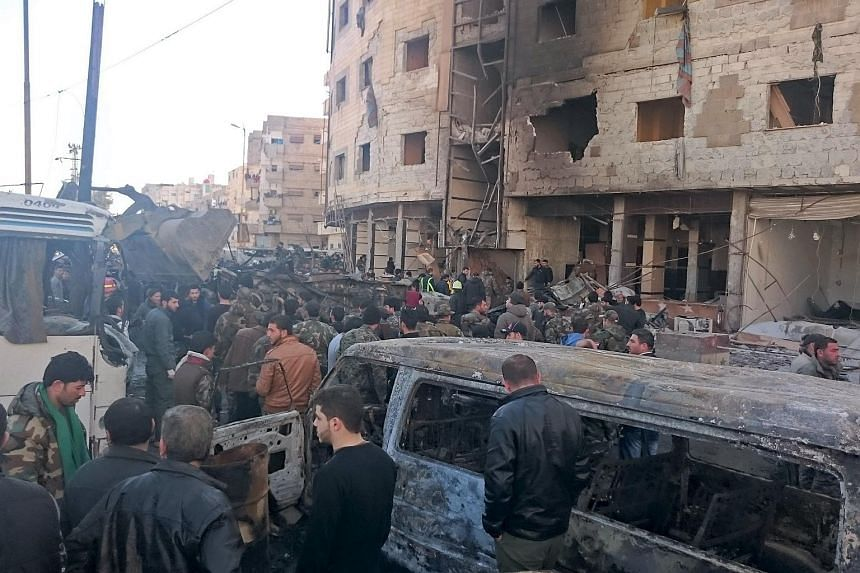 Residents and soldiers loyal to Syria's President Bashar al-Assad inspect damage after a suicide attack in Damascus, on Jan 31, 2016.
