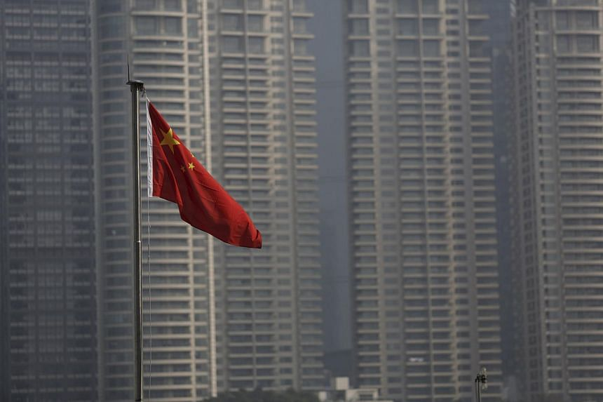 A Chinese flag is seen in front of the financial district of Pudong in Shanghai, China.