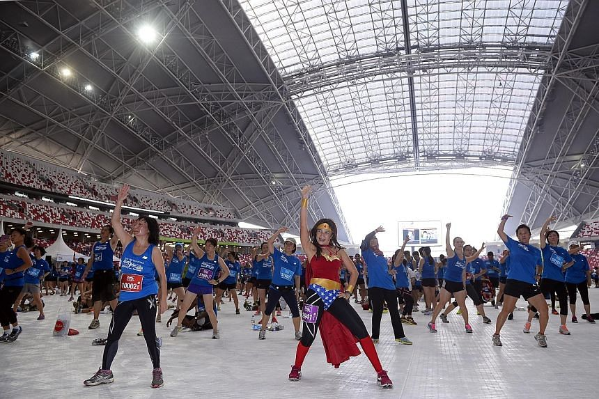 Those who completed The Straits Times Run in 2014 participating in Zumba exercises at the Sports Hub. The registration for this year's May 22 race event starts from the middle of this month.