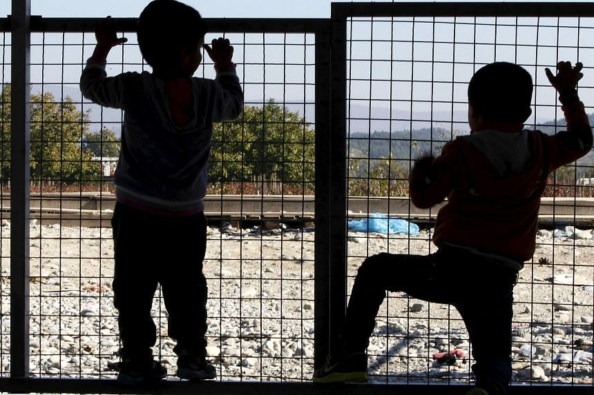 Two migrant children waiting for transport at a transit camp in Gevgelija, Macedonia, after entering the country. They had been taken across the border with Greece in November.