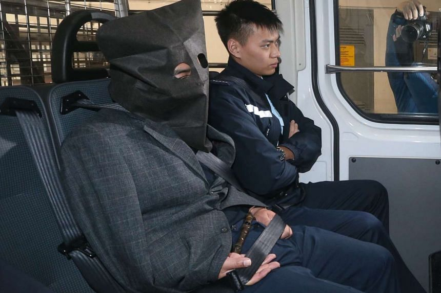Chinese national Shi Deyun (left) arrives in a police van at a court of justice in Hong Kong.