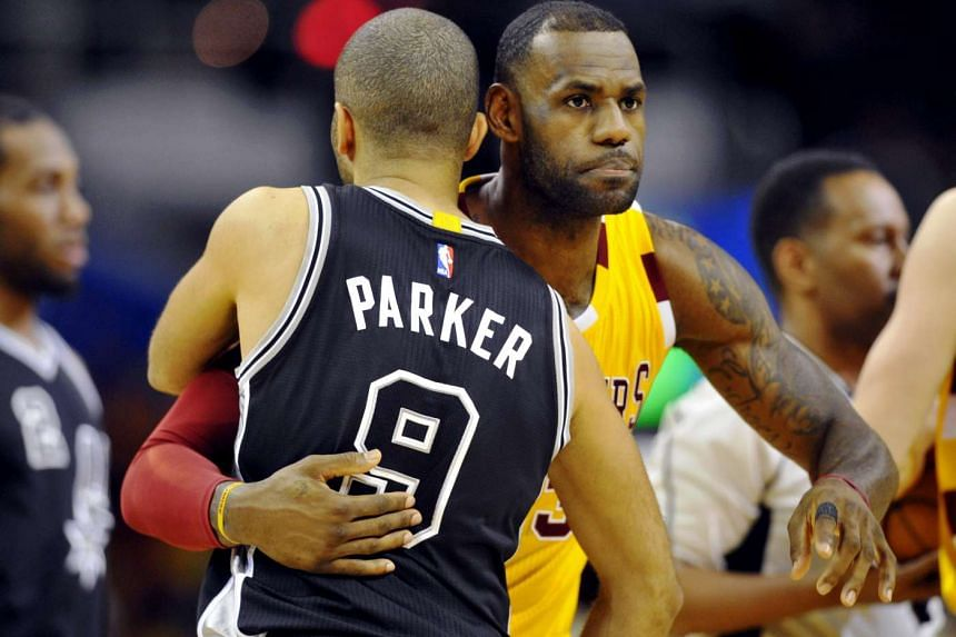 San Antonio Spurs guard Tony Parker (9) hugs Cleveland Cavaliers forward LeBron James (23) prior to their game in Cleveland.