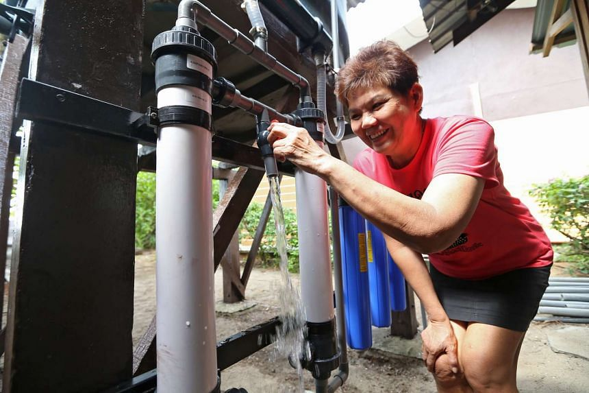 Madam Koh Siew Hong (above), 64, using the water treatment system at her food outlet Season Life Seafood on Pulau Ubin yesterday.