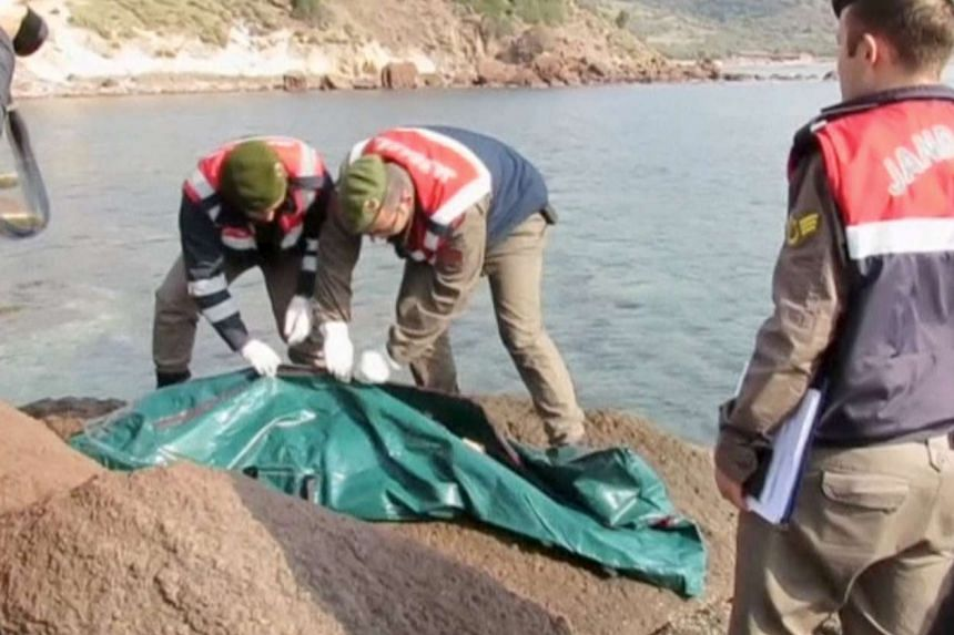 Soldiers covering a body (above) that was among those washed up on a Turkish beach after a migrant boat sank off Ayvacik.