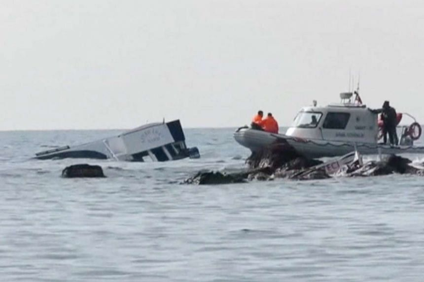 Soldiers covering a body that was among those washed up on a Turkish beach after a migrant boat sank (above) off Ayvacik.