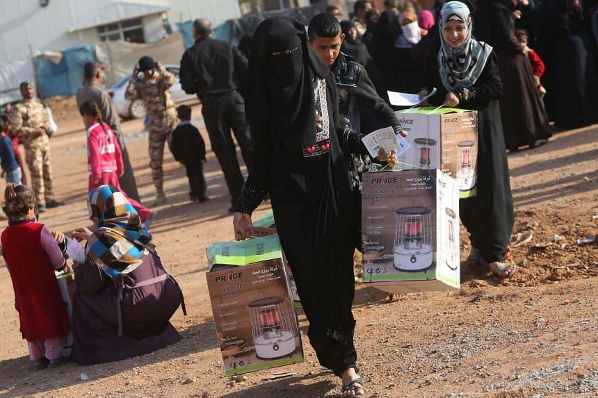 Displaced Iraqis gather as humanitarian aid is distributed on Dec 16, 2015.