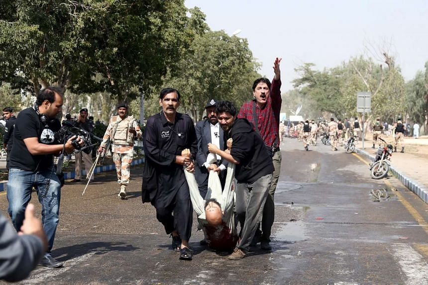 People carry a man who was injured during an anti-government protest in Karachi, Pakistan, Feb 02 2016.
