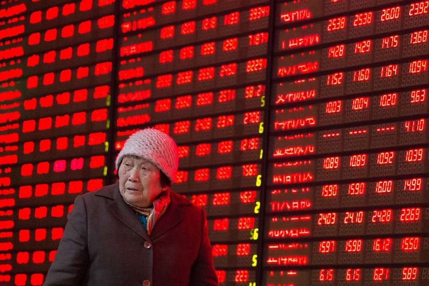 An investor walks past an electronic screen showing stock information at a brokerage house in Nanjing.