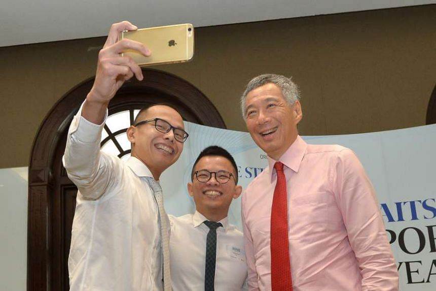 Owners of French restaurant chain Saveur Joshua Khoo and Dylan Ong taking a selfie with PM Lee.