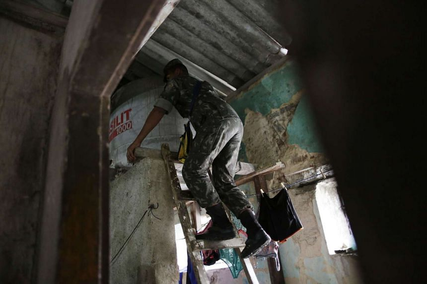 Brazilian soldier conducts an inspection for the Aedes aegypti mosquito in a house in Recife, Brazil, on Feb 1, 2016.
