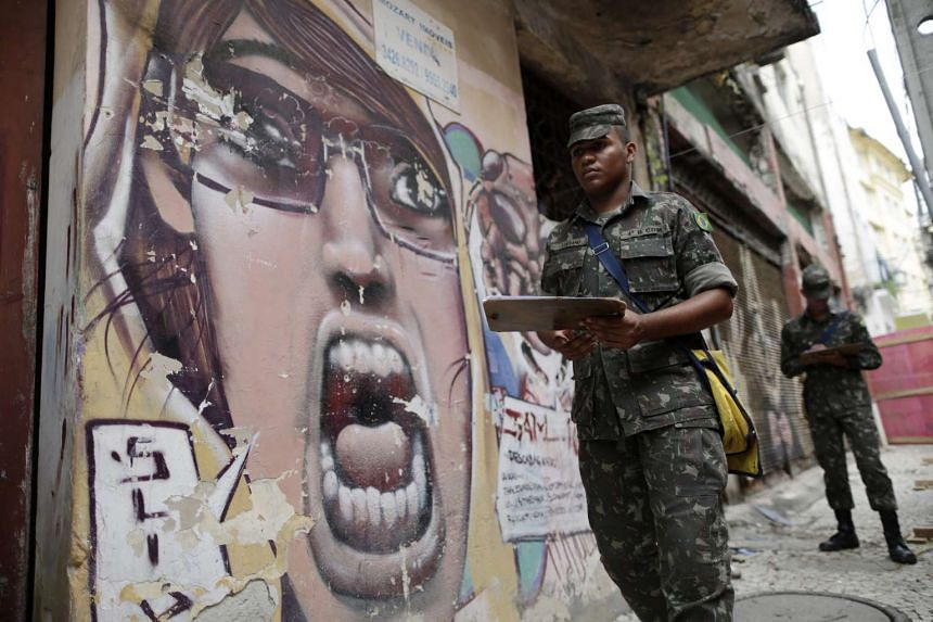 Brazilian soldiers conduct an inspection for the Aedes aegypti mosquito on a street in Recife, Brazil, on Feb 1, 2016.