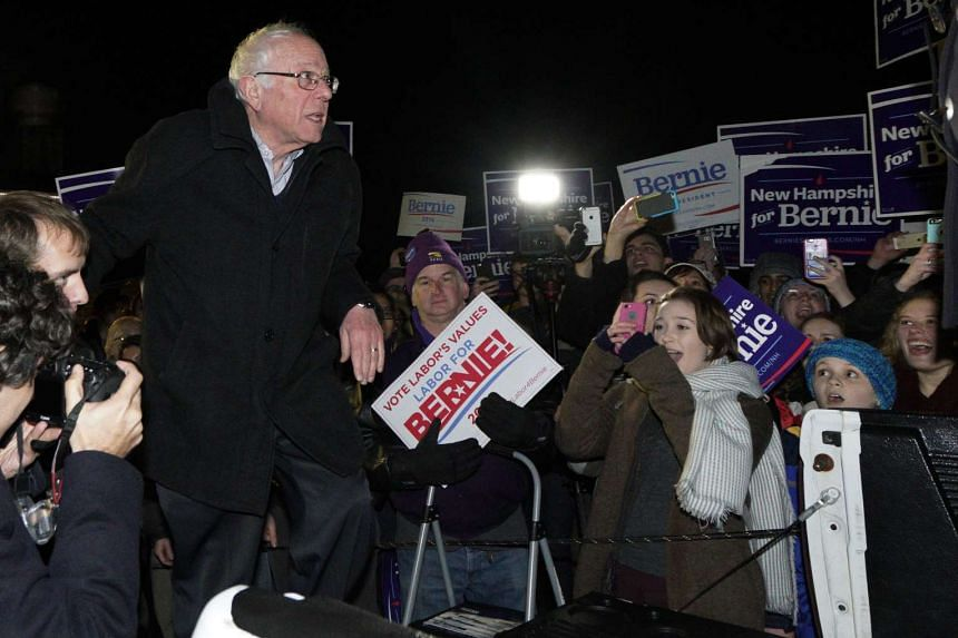 US Democratic presidential candidate Bernie Sanders climbs into the bed of a pickup truck to address supporters after arriving early morning in Bow, New Hampshire on Feb 2, 2016.